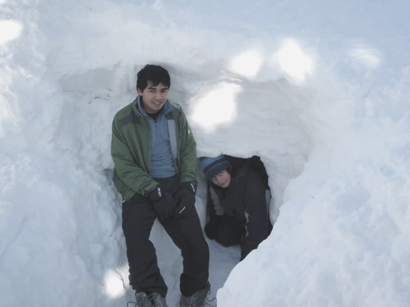 Two Backpacking Scouts exiting snow cave
