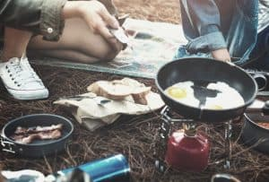 backpackers cooking breakfast on canister stove