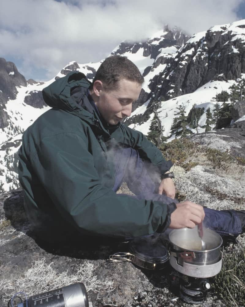 Backpacker cooking on camp stove