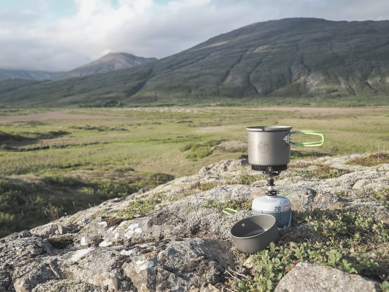 backpacking stove on outcrop looking over valley