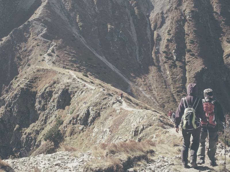 hikers hiking along mountainside