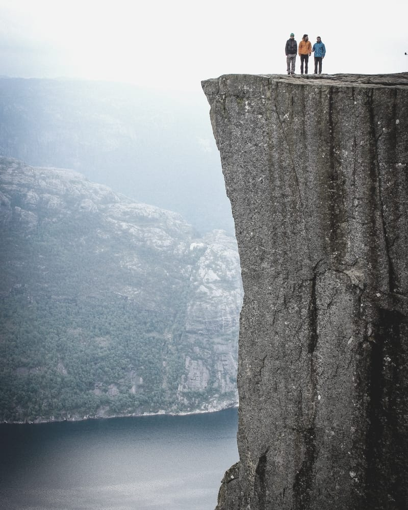 three hikers standing on top of cliff edge