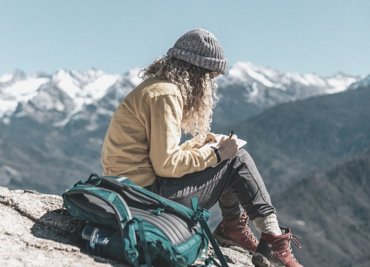 Hiker writing in notebook overlooking mountain range