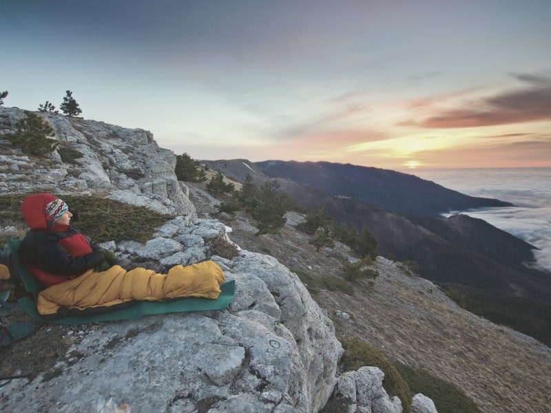 Backpacker in sleeping bag on cliff watching sunset