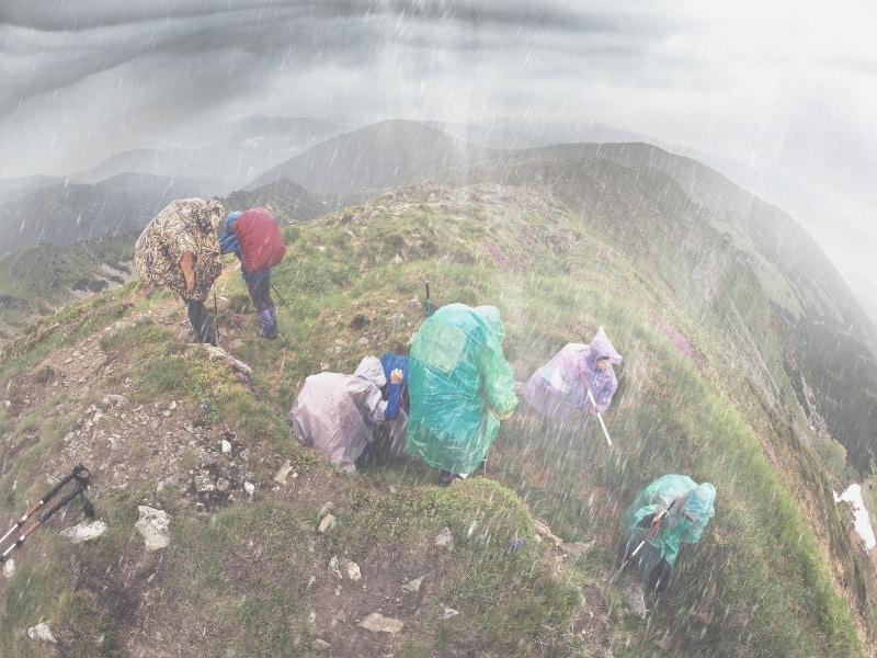 Backpackers in heavy rain on mountain ridge
