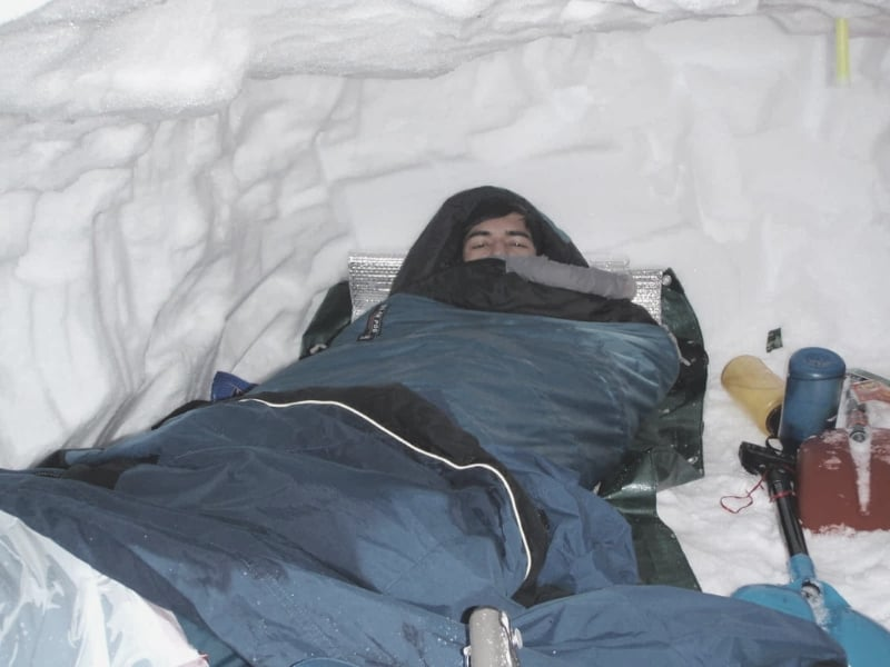 Scout sleeping in sleeping bag in snow cave