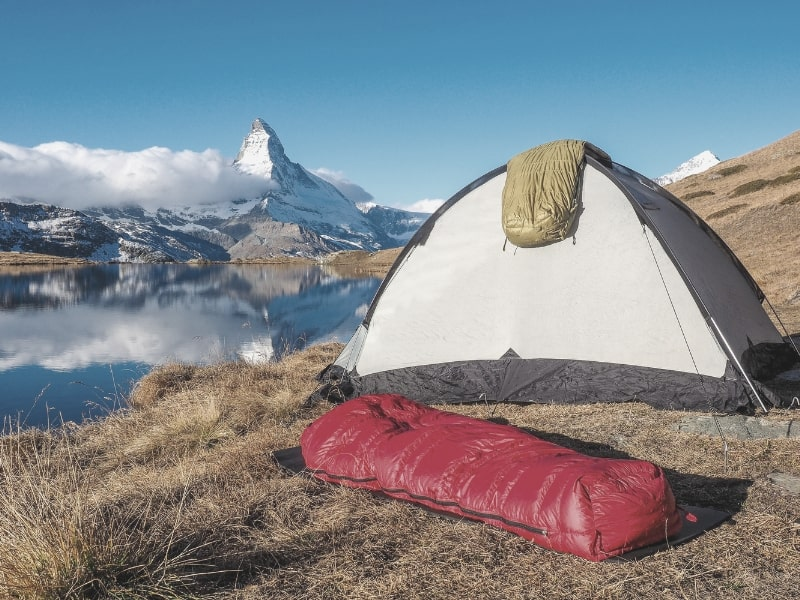 Sleeping Bags & Tent in front of glacial lake and mountain