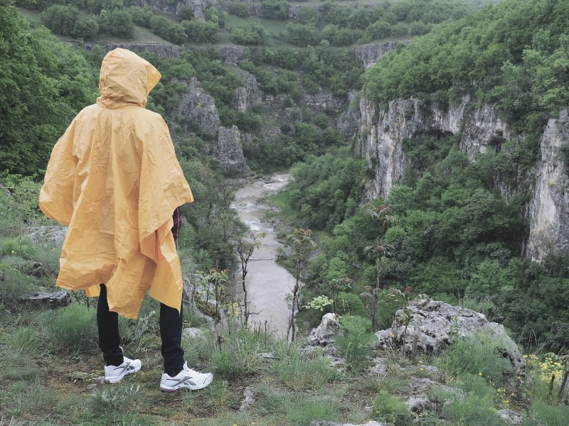 hiker wearing poncho overlooking canyon