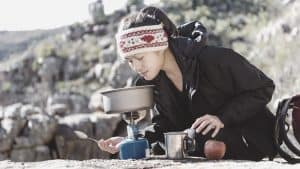 women backpacker cooking on backpacking stove