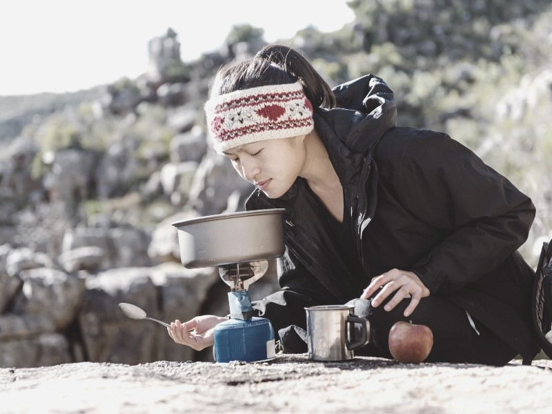 women backpacker cooking on backpacking stove_intext