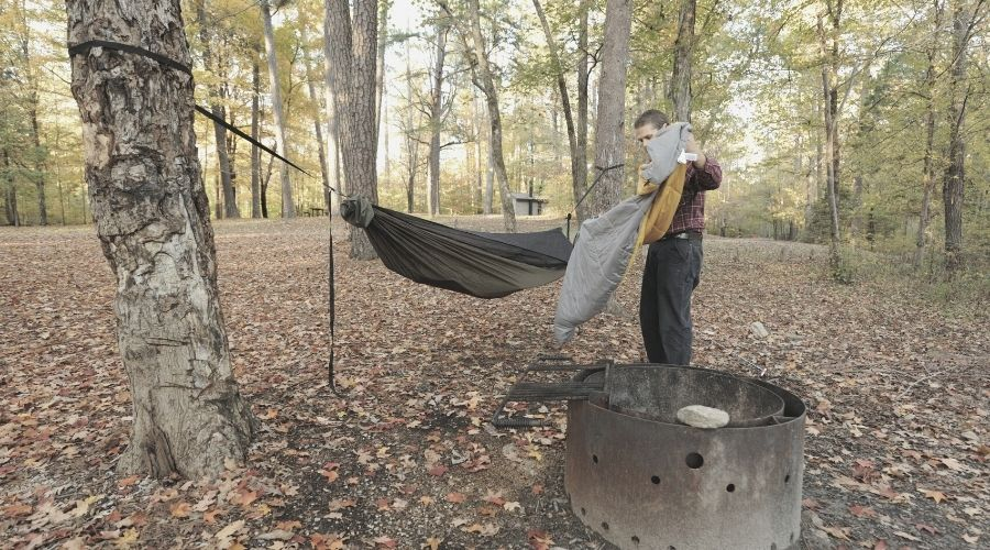 backpacker putting sleeping bag in hammock