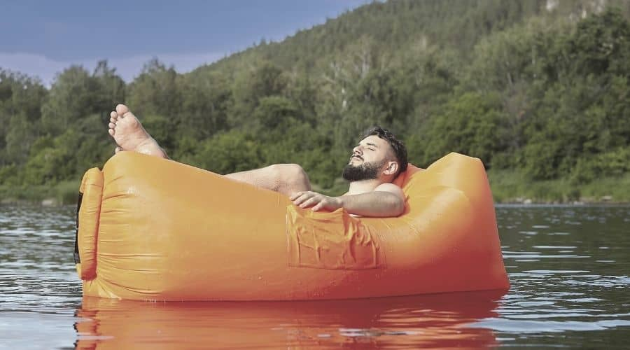 man sitting on air sofa in lake