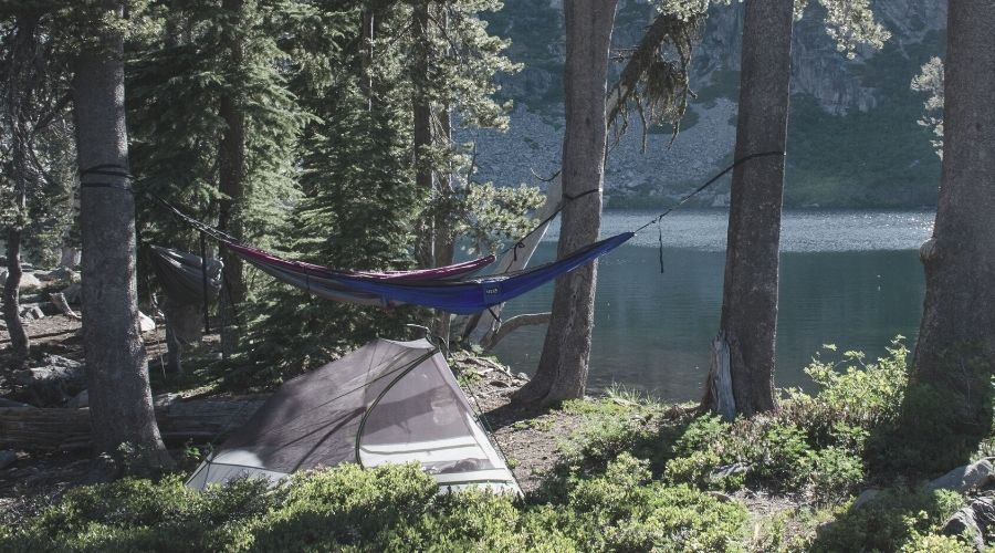 tent and two hammocks by a lake shore